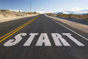 new beginnings, travel and adventure concept - close up of word start on suburban asphalt road