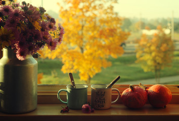 two cups of coffee,pumpkins and an autumn bouquet on the windowsill against  beautiful autumn view