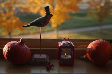 wooden bullfinch,pumpkins,lantern on the windowsill against autumn view/anniversary/thanksgiving/ grandparent'sday/mother's day background