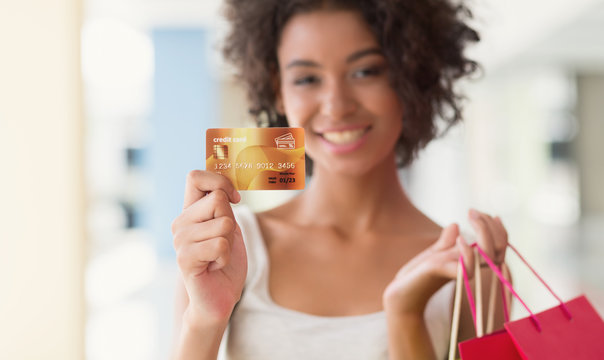 Young african-american woman holding colourful bags and credit card
