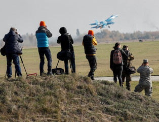 Journalists take pictures as a Ukrainian Su-27 fighter jet takes off during the Clear Sky 2018 multinational military drills in Starokostiantyniv