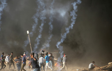 Palestinians hurl stones at Israeli troops during a protest at the Israel-Gaza border fence in the southern Gaza Strip