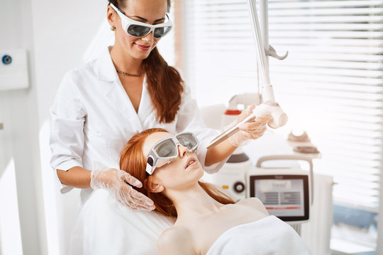 Ginger haied girl undergoes a procedure of laser rejuvenation at luxury cosmetological salon to keep her skin fresh and elastic. Apparatus cosmetology Concept