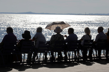 People are seen in silhouette and take advantage of warm autumn weather along the Promenade des Anglais
