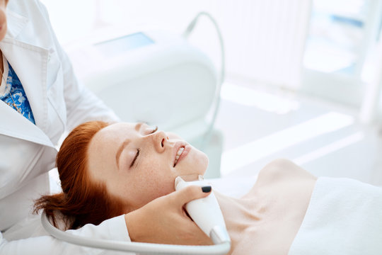 Apparatus face treatment in medical spa center, beautiful redhead lady receiving electric facial peeling massage. Cosmetological methods, apparatus cosmetology, SPA-procedures Concept.