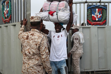 Soldiers of border security control the entrance of Haitians who expect to cross the border to market their products in Dajabon