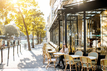 Street view on the traditional french cafe with young woman sitting outdoors during the morning light in Paris Fototapete