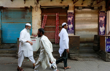 People walk past in front of closed meat shops in Gurugram