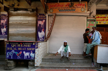 People sit outside the closed meat shops in Gurugram
