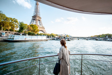 Poster de jardin Paris Young woman enjoying beautiful landscape view on the riverside with Eiffel tower from the boat during the sunset in Paris