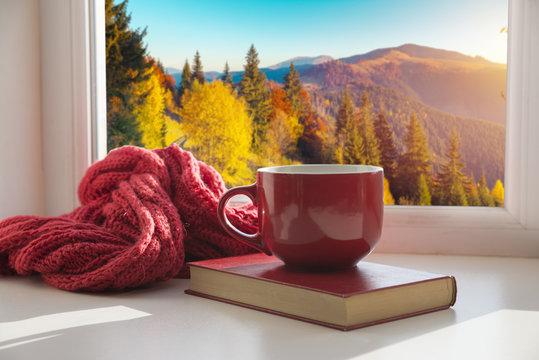 window with autumn leaves, a book, a mug of tea