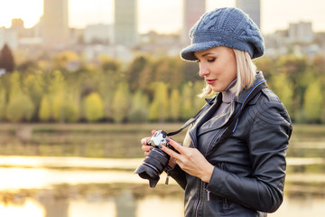 stylish blonde woman in blue french beret photographer takes pictures of autumn forest at sunset