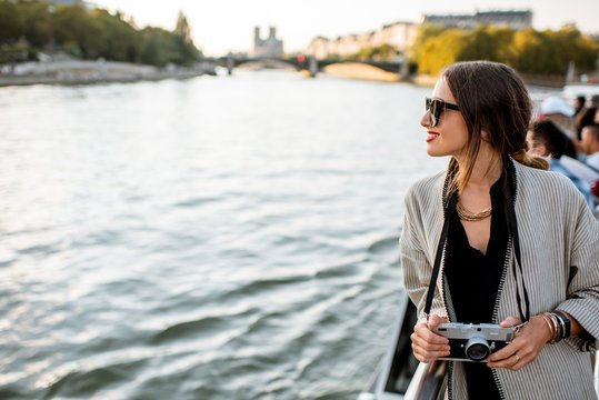 Young woman enjoying beautiful landscape view on the riverside from the ship during the sunset in Paris