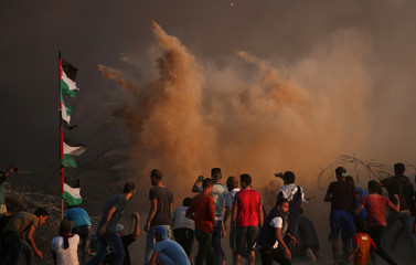 Palestinian demonstrators react during a protest at the Israel-Gaza border fence in the southern Gaza Strip