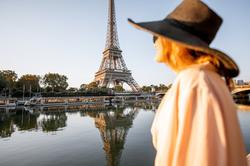 Young woman tourist enjoying landscape view on the Eiffel tower with beautiful reflection on the water during the mornign light in Paris. Image focused on the background