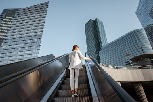 Stylish businesswoman in white suit going up on the escalator at the business centre outdoors with skyscrapers on the background in Paris