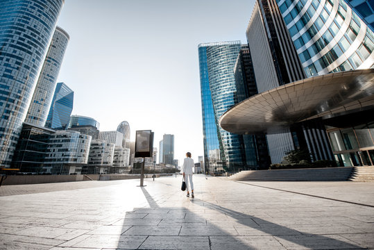 Business woman at the financial district with beautiful skyscrapers on the background during the morning light in Paris. Wide panoramic view