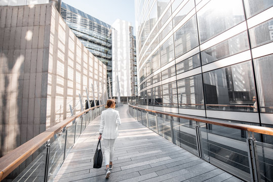Business woman walking outdoors at the financial district with modern buildings on the background in Paris