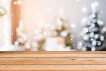abstract blurred interior christmas tree in sweet house with snow falling and wood plank for show,promote product concept
