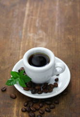 a cup of black coffee with roasted coffee beans and leaves on white background