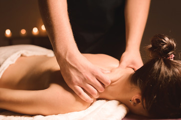 Men's hands make a therapeutic neck massage for a girl lying on a massage couch in a massage spa...