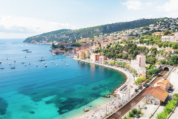 Bathers enjoy at the beach of the beautiful bay of Villefranche-sur-Mer on the Cote D'Azur