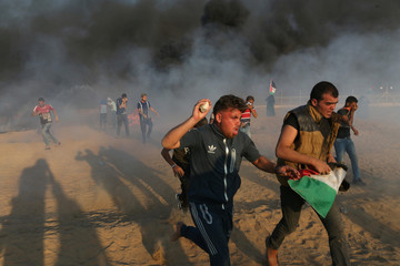 Palestinian demonstrators run during a protest at the Israel-Gaza border fence in the southern Gaza Strip