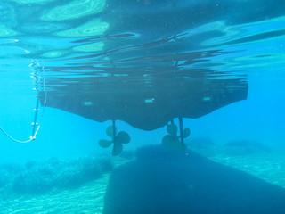 Underwater view of yacht bottom, 2 propellers, water plants in Kolona double bay Kythnos island Cyclades Greece, Aegean sea.