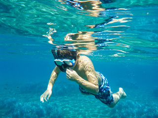 Boy in mask for scuba diving swimming underwater in Kolona double bay Kythnos island Cyclades Greece, Aegean sea.