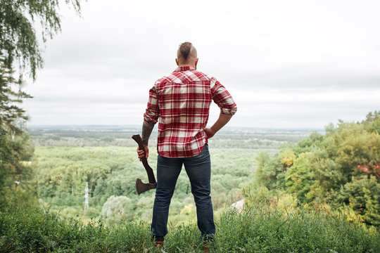 Rear back view of lumberjack in forest holding an axe on his shoulder