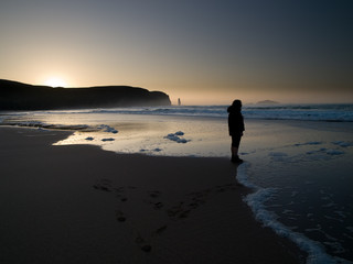A figure stands at Sandwood Bay at Sunset