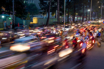 Dense traffic at night intersection with blurred lights passing through motorbikes and vehicles. Fotomurales