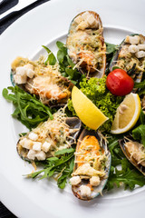 Mussels baked with herbs, white wine and Parmesan.
