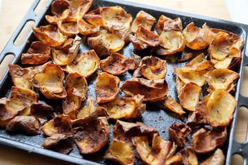Baked potato skin crisps on a tray.