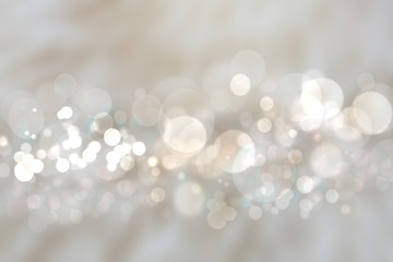 Abstract silver background texture with blurred white bokeh light circles.