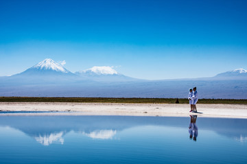 Cejar salt pool, Atacama Desert, Chile with 2 people in bathrobes and volcanoes in the background against a clear blue sky