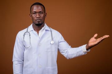 Handsome African man doctor wearing eyeglasses against brown bac
