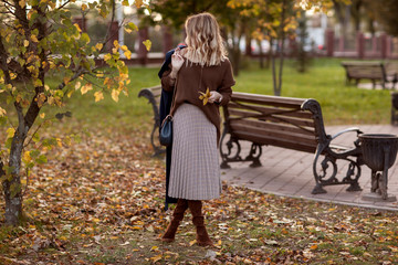 A beautiful fashionable woman is standing in an autumn park in a brown sweater and a long plaid skirt with a bag in her hands.