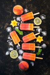 Peach popsicles with fruits and ice cubes on a dark grunge background. Top view, flat lay.