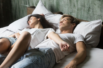 Young attractive relaxing girl and guy sleeping in casual clothes on bed in bedroom at home. Couple in love, view from above. Lazy weekend free time, relaxation resting after working day, sleep