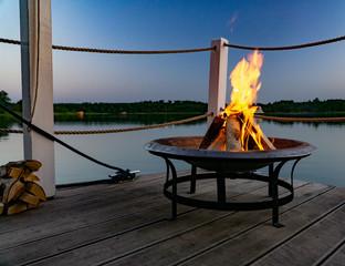 Feuer in einer Feuerschale am Abend am See