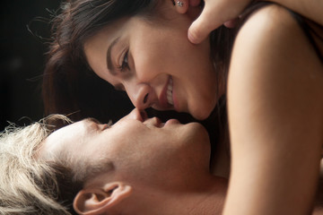 Close up young attractive smiling couple faces lying and looking at each other with tenderness and love before kissing. Head shot of lovers, foreplay before having sex. Newlyweds enjoy weekend concept