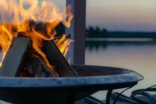 Flammen in einer Feuerschale in der Dämmerung am See