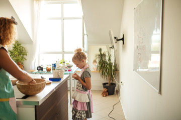 Caucasian pretty young woman and her little cute daughter in apron are cooking at the white well-lit kitchen with big window.