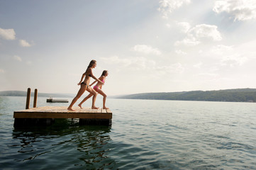 Full length of female friends jumping from floating platform in lake against sky