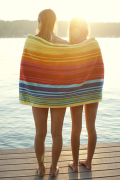 Rear view of friends wrapped in towel, standing on jetty
