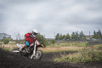 Young biker riding dirt bikes on field against cloudy sky