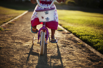 Low section of girl riding bicycle on footpath in park