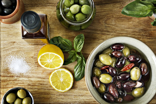 Olives and olive oil on wooden cutting board