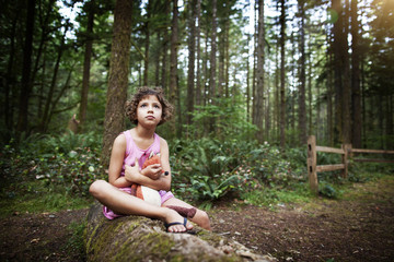 Thoughtful girl sitting on fallen tree while holding toy in forest
